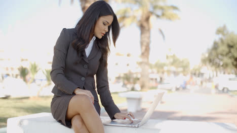 Business-Woman-With-Laptop-Sitting-On-The-Bench