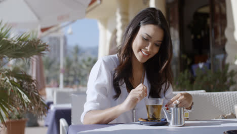 Girl-Sitting-At-Cafe-With-Cup-Of-Tea