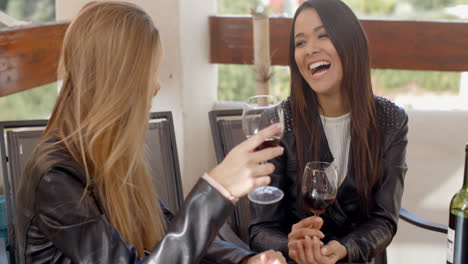 Woman-laughing-with-friend-over-wine