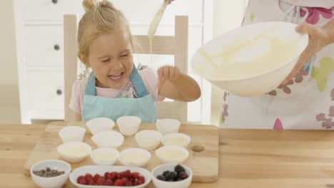 Girl-laughing-as-batter-is-poured-into-muffin-cups