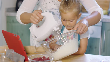 Little-girl-watching-her-mother-whisk-cream