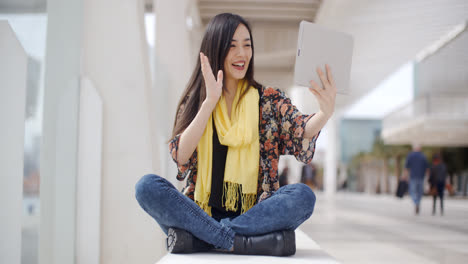Smiling-woman-waving-at-her-tablet-computer