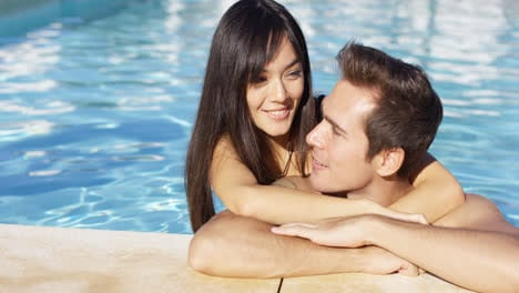 Handsome-smiling-couple-cuddles-in-swimming-pool