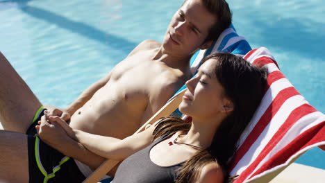 Young-couple-relaxing-poolside-in-deck-chairs