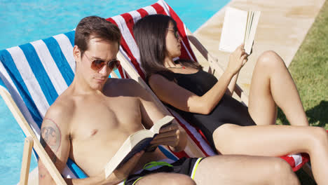 Relaxed-attractive-young-couple-reading-poolside