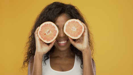 Excited-woman-playing-with-grapefruit