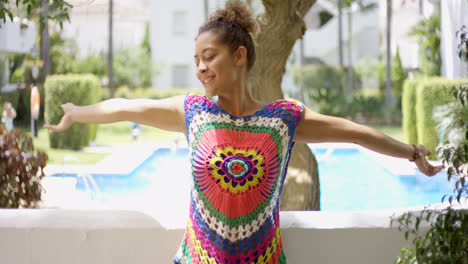 Woman-in-colorful-knit-top-stretching-on-balcony