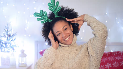 Playful-young-woman-wearing-green-reindeer-antlers