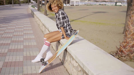 Happy-trendy-young-woman-with-a-skateboard