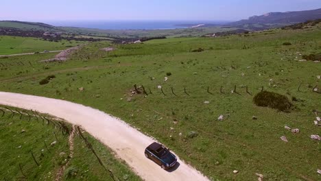 Aerial-View-Of-Driving-Car-On-Hilly-Terrain