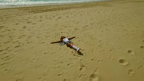 Young-woman-lying-on-her-back-on-a-beach