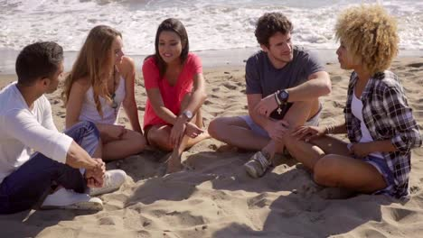 Group-of-diverse-young-friends-chatting-on-a-beach