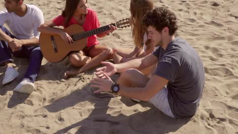 Young-friends-relaxing-on-a-beach-playing-guitar