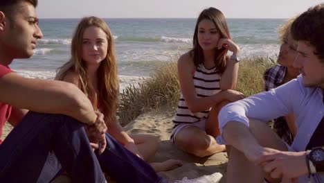 Group-Of-Young-People-Sitting-On-The-Sandy-Beach