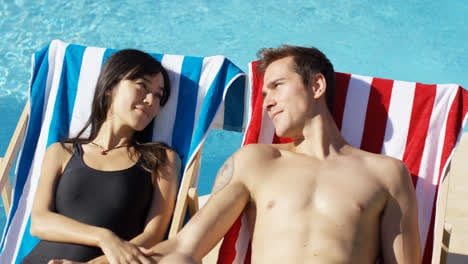 Contented-young-couple-smiling-as-they-sunbathe