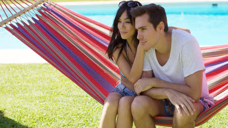 Affectionate-young-couple-sitting-on-a-hammock