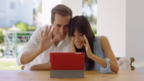Man-and-woman-waving-at-their-tablet-computer