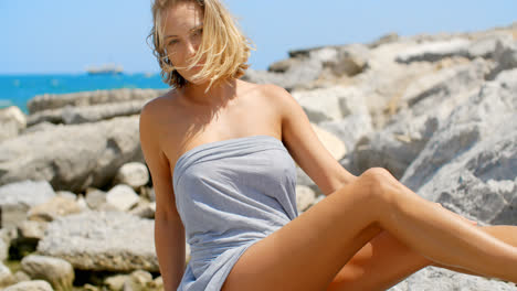 Woman-Wrapped-in-Grey-Fabric-at-Rocky-Ocean-Shore