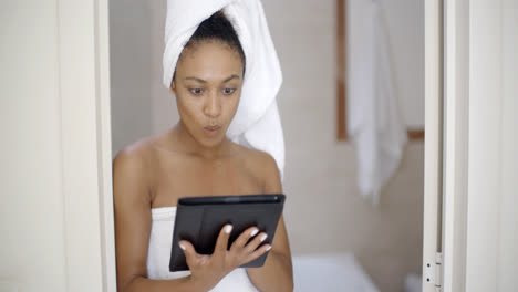 Young-Woman-Wearing-Bath-Towel-Using-Tablet-Computer