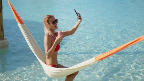 Female-tourist-drinking-cocktail-and-taking-selfie-on-hammock