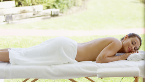 Woman-only-wearing-towel-rests-on-table-in-spa