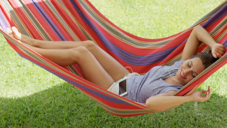 Happy-young-woman-relaxing-in-a-colorful-hammock