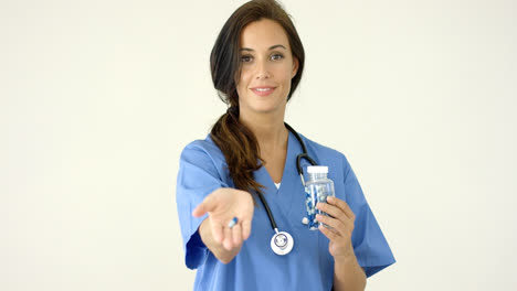 Attractive-female-doctor-holding-out-a-pill