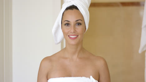 Smiling-brunette-wearing-white-towel-on-head