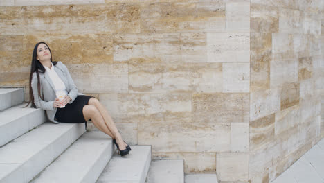 Young-business-woman-on-stairs-drinking-coffee