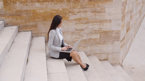 Side-view-of-woman-using-laptop-on-stairs