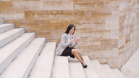 Pretty-business-woman-sitting-on-steps-using-phone