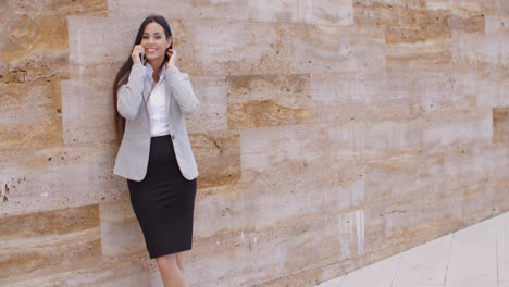 Pretty-woman-talking-on-phone-and-leaning-on-wall