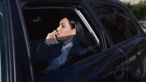Serious-young-executive-on-phone-in-limousine