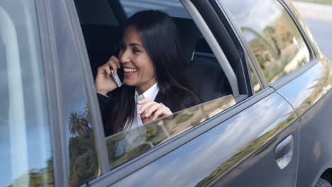 Laughing-young-executive-on-phone-in-car