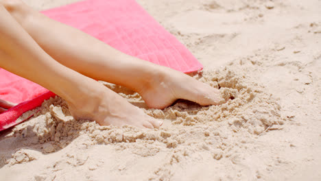 Close-up-Woman-Feet-Resting-on-Beach-Sand