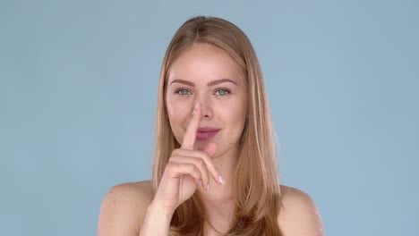 Beautiful-blond-woman-making-quiet-gesture-with-finger-on-her-lips