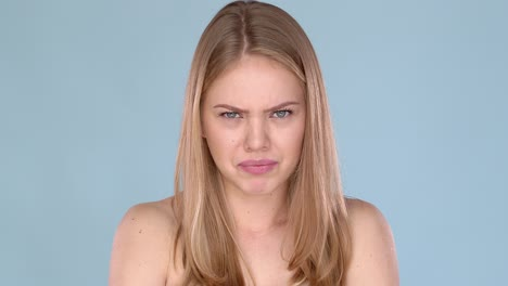 Angry-young-female-blond-hair-with-bare-shoulders-Frustrated-emotions-on-her-face