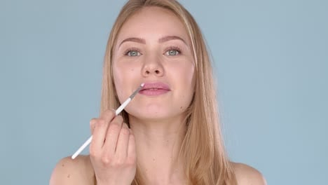 Adorable-blond-woman-apllying-lipgloss-using-cosmetic-brush