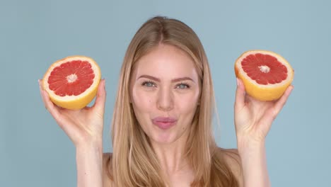 Slow-motion-video-of-a-beautiful-happy-smiling-young-blonde-woman-with-grapefruit-halfs