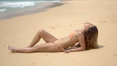 Slim-woman-sunbathing-on-beach