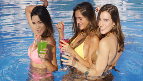 Three-gorgeous-women-in-pool-with-colorful-drinks