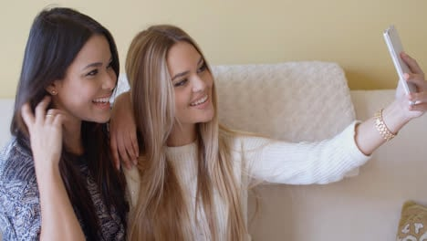 Two-young-girlfriends-taking-a-selfie-at-home