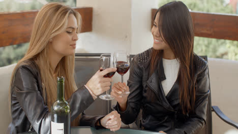 Two-attractive-girls-sitting-on-balcony-with-wine