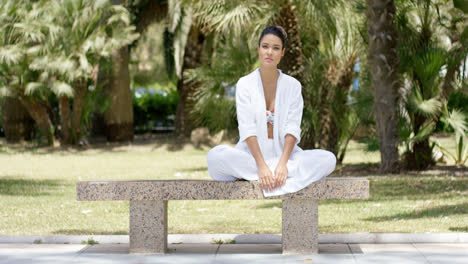 Enthusiastic-woman-sitting-on-granite-bench