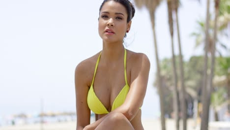 Serious-woman-in-yellow-bikini-sitting-near-beach