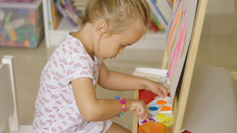 Cute-little-girl-mixing-paints-for-her-painting