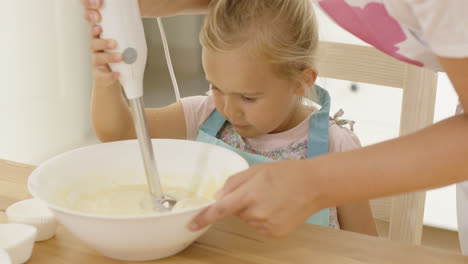 Cute-little-girl-learning-to-bake-from-mother