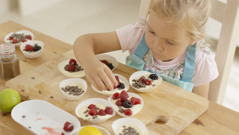 Girl-putting-berries-on-muffins-on-table