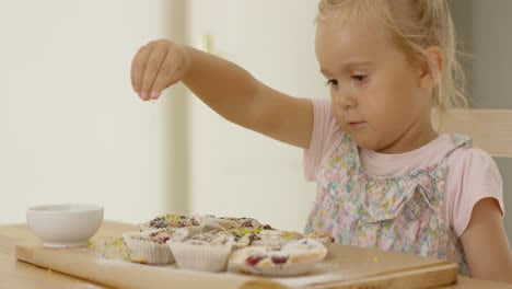 Close-up-on-girl-sprinkling-toppings-on-muffins