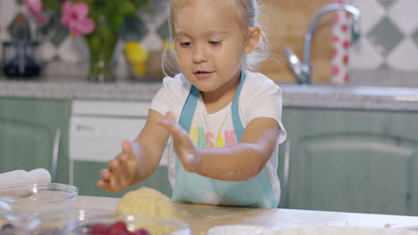 Little-girl-having-fun-kneading-the-pastry